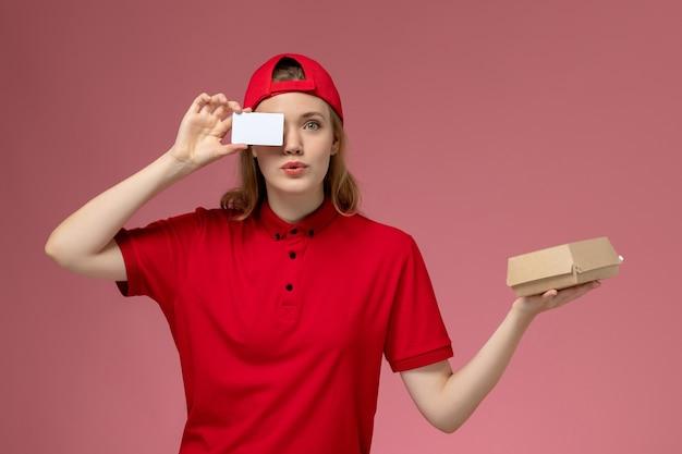 Widok z przodu kurierka w czerwonym mundurze i pelerynie trzymająca małą paczkę z dostawą żywności z białą plastikową kartą na różowej ścianie, dostawa munduru służbowego