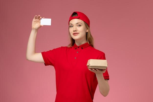 Widok z przodu kurierka w czerwonym mundurze i pelerynie trzymająca małą paczkę z dostawą żywności z białą plastikową kartą na różowej ścianie, jednolita usługa dostawy