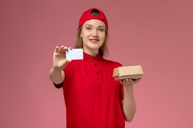 Widok z przodu kurierka w czerwonym mundurze i pelerynie trzymająca małą paczkę z jedzeniem na dostawę z białą plastikową kartą na różowej ścianie, jednolita usługa dostawy praca pracownika