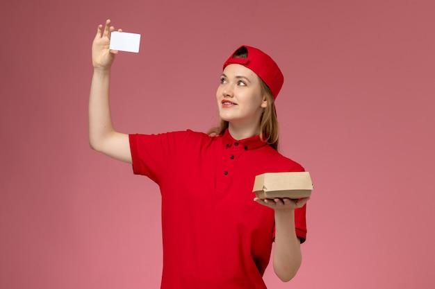 Widok z przodu kurierka w czerwonym mundurze i pelerynie trzymająca małą paczkę z jedzeniem na dostawę z białą plastikową kartą na różowej ścianie, pracownik służbowy w mundurze dostawy