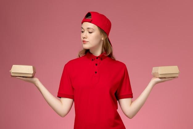 Widok z przodu kurierka w czerwonym mundurze i pelerynie trzymająca małe paczki z żywnością na różowej ścianie, mundur firmy świadczącej usługi dostawcze