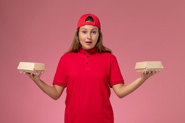 Widok z przodu kurierka w czerwonym mundurze i pelerynie trzymająca paczki z dostawą żywności na jasnoróżowej ścianie, jednolita dziewczyna z dostawcą usług kurierskich