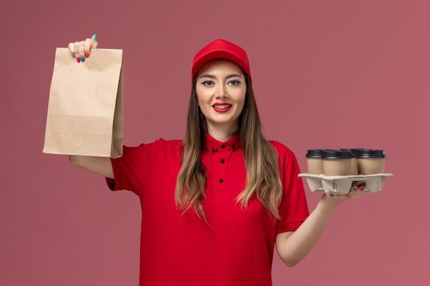 Widok z przodu kurierka w czerwonym mundurze trzyma filiżanki kawy dostawy z pakietem żywności na różowym mundurze dostawy usług biurowych