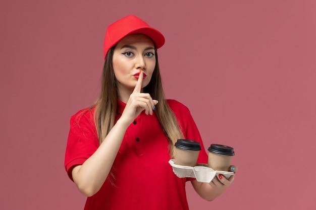 Widok z przodu kurierka w czerwonym mundurze, trzymająca brązowe filiżanki do kawy z dostawą, pokazująca znak ciszy na jasnoróżowym tle