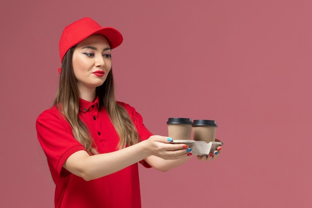 Widok z przodu kurierka w czerwonym mundurze, trzymająca brązowe filiżanki kawy dostawy na jasnoróżowym tle