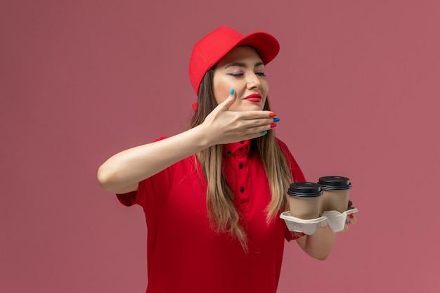 Widok z przodu kurierka w czerwonym mundurze, trzymająca brązowe filiżanki kawy dostawy, pachnące na jasnoróżowym tle mundur dostawy usług