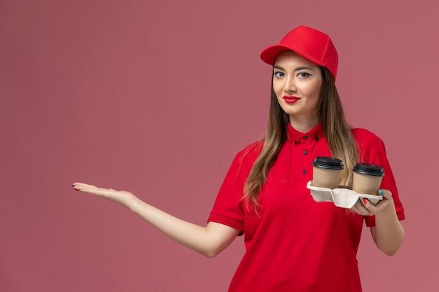 Widok z przodu kurierka w czerwonym mundurze, trzymająca brązowe filiżanki kawy na jasnoróżowym tle firma świadcząca usługi