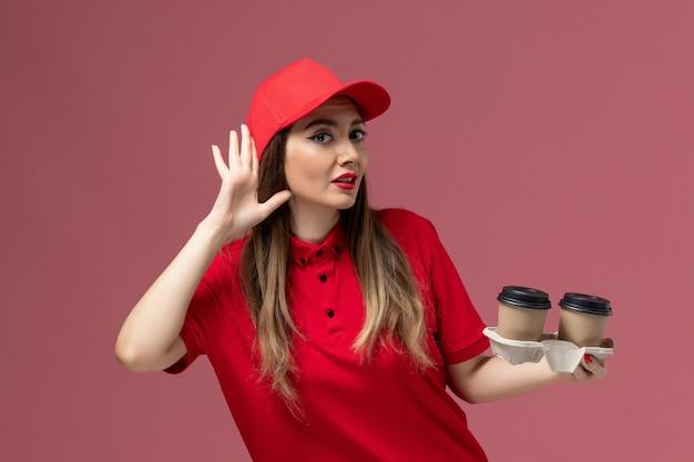 Widok z przodu kurierka w czerwonym mundurze, trzymająca brązowe filiżanki kawy z dostawą, próbująca usłyszeć na jasnoróżowym tle mundur dostawy usług
