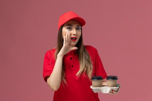 Widok z przodu kurierka w czerwonym mundurze trzymająca brązowe filiżanki kawy z dostawą szepcząca na jasnoróżowym tle świadczenie usług w mundurze pracownik praca firma kobieca
