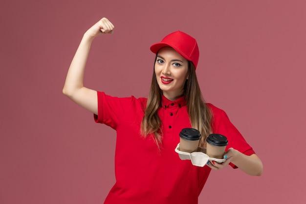 Widok z przodu kurierka w czerwonym mundurze, trzymająca brązowe filiżanki kawy z dostawą, zginająca się na jasnoróżowym tle