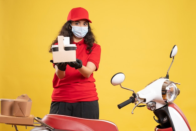 Widok z przodu kurierka w czerwonym mundurze trzymająca kawę na żółtym tle dostawa covid-usługa mundurowa pracownik pandemiczny praca