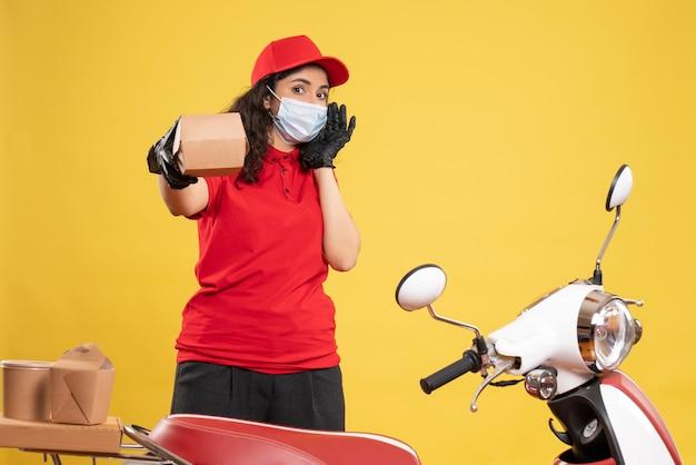 Widok z przodu kurierka w czerwonym mundurze trzymająca małą paczkę żywności na żółtym tle covid - pandemia pracownika usługi dostarczania pracy delivery