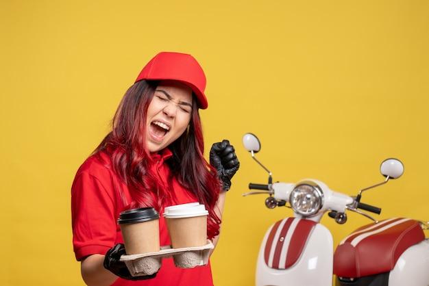 Widok z przodu kurierka w czerwonym mundurze z kawą na żółtej ścianie