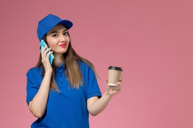 Widok z przodu kurierka w niebieskim mundurze i pelerynie, trzymając filiżankę kawy dostawy i rozmawia przez telefon na różowym biurku