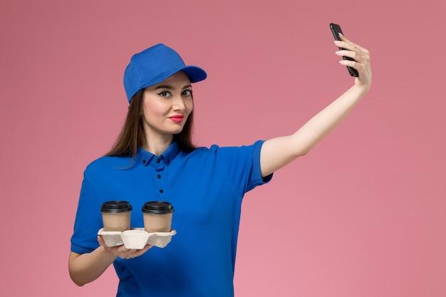 Widok z przodu kurierka w niebieskim mundurze i pelerynie, trzymając filiżanki kawy dostawy robiąc zdjęcie na różowej ścianie