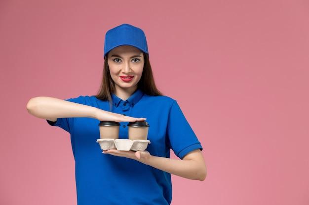 Widok z przodu kurierka w niebieskim mundurze i pelerynie, trzymając filiżanki kawy dostawy uśmiechnięte na różowej ścianie