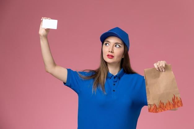 Widok z przodu kurierka w niebieskim mundurze i pelerynie trzymająca białą kartkę i papierowe opakowanie żywności na różowej ścianie