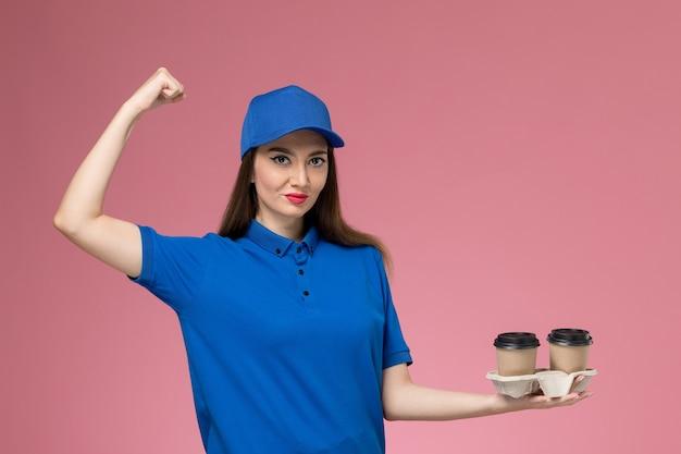 Widok z przodu kurierka w niebieskim mundurze i pelerynie, trzymająca filiżanki kawy z dostawą i zginająca się na różowej ścianie