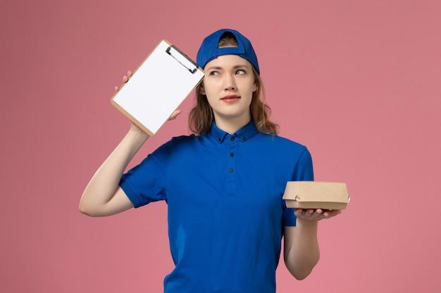 Widok z przodu kurierka w niebieskim mundurze i pelerynie trzymająca małą paczkę z dostawą żywności i myślący notatnik na różowej ścianie, pracownik dostawy