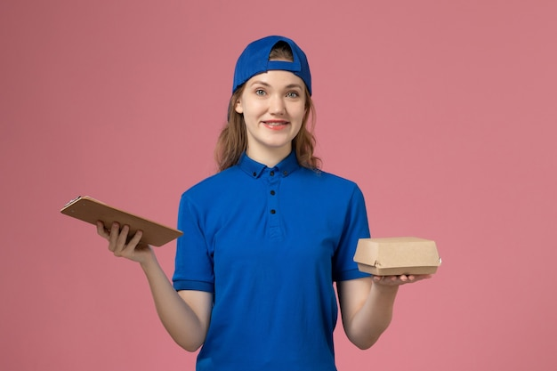Widok z przodu kurierka w niebieskim mundurze i pelerynie trzymająca małą paczkę z dostawą żywności i notatnik na różowej ścianie, dziewczyna doręczycielka