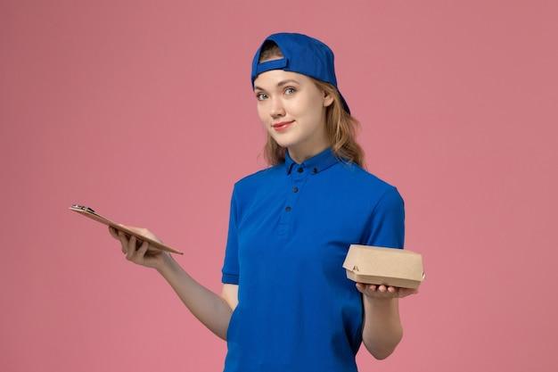 Widok z przodu kurierka w niebieskim mundurze i pelerynie trzymająca małą paczkę z dostawą żywności i notatnik na różowej ścianie, pracownik dostawy