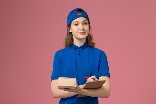 Widok z przodu kurierka w niebieskim mundurze i pelerynie trzymająca małą paczkę z dostawą żywności i notatnik piszący na różowej ścianie, pracownik dostawy