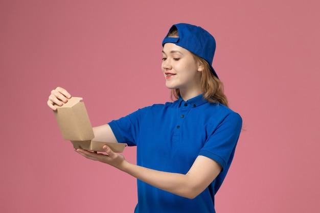 Widok z przodu kurierka w niebieskim mundurze i pelerynie trzymająca małą paczkę z dostawą żywności, otwierając ją na różowej ścianie, pracownik służby munduru dostawy