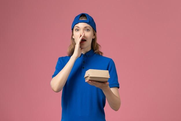Widok z przodu kurierka w niebieskim mundurze i pelerynie trzymająca małą paczkę z dostawą żywności, wzywająca na różowej ścianie, firma usługowa mundurowa dostawy