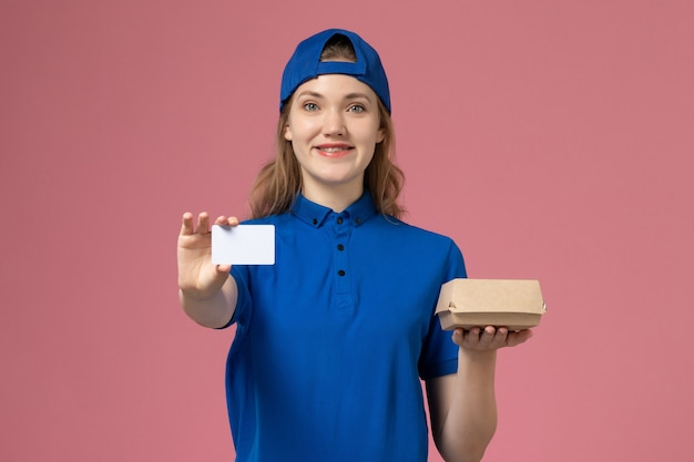 Widok z przodu kurierka w niebieskim mundurze i pelerynie trzymająca małą paczkę z jedzeniem na dostawę z kartą na różowej ścianie, pracownik usług dostawy pracy