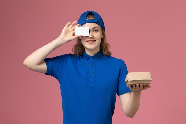 Widok z przodu kurierka w niebieskim mundurze i pelerynie trzymająca małą paczkę żywnościową z kartą na różowej ścianie, praca pracownika dostawy