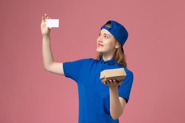 Widok z przodu kurierka w niebieskim mundurze i pelerynie trzymająca małą paczkę żywnościową z kartą na różowej ścianie, praca pracownika firmy kurierskiej