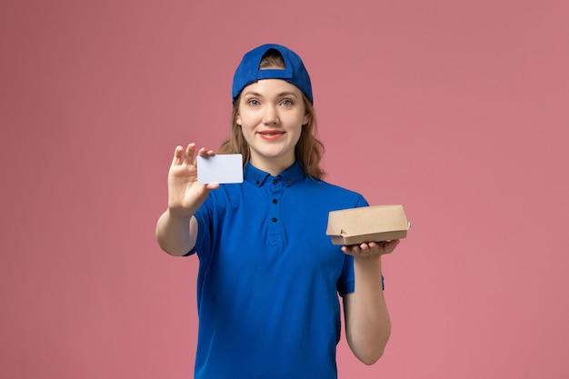 Widok z przodu kurierka w niebieskim mundurze i pelerynie trzymająca małą paczkę żywnościową z kartą na różowej ścianie, pracownik biura dostawy pracy