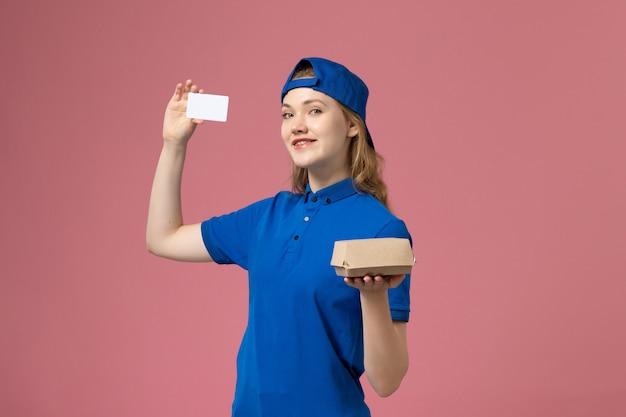 Widok z przodu kurierka w niebieskim mundurze i pelerynie trzymająca małą paczkę żywnościową z kartą na różowej ścianie, pracownik biura dostawy