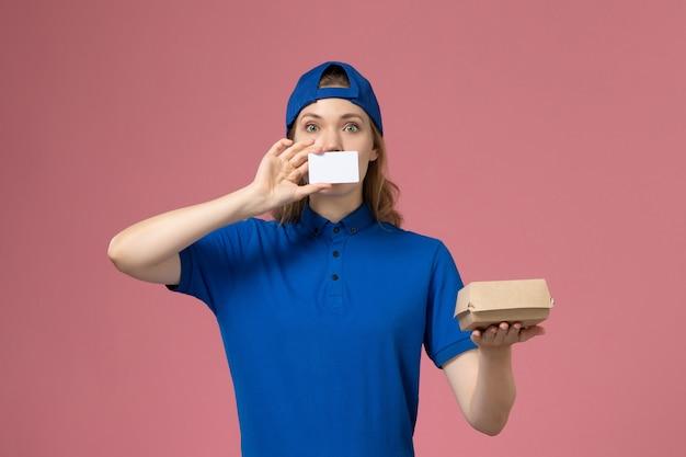 Widok z przodu kurierka w niebieskim mundurze i pelerynie trzymająca małą paczkę żywnościową z kartą na różowej ścianie, pracownik dostawy