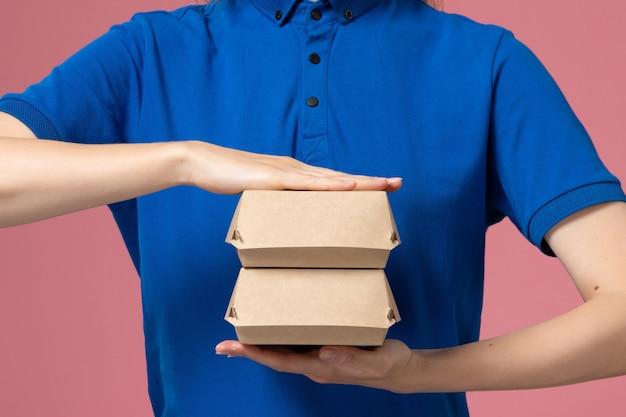 Widok z przodu kurierka w niebieskim mundurze i pelerynie trzymająca małe opakowania z dostawą żywności na różowej ścianie, praca w firmie usługowej w mundurze dostawy