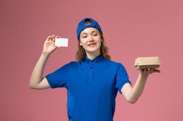 Widok z przodu kurierka w niebieskim mundurze i pelerynie trzymająca mały pakiet żywnościowy z kartą na różowej ścianie, pracownik dostawy