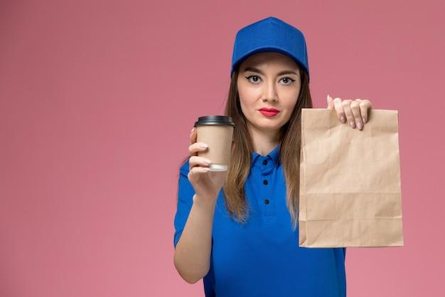 Widok z przodu kurierka w niebieskim mundurze i pelerynie trzymającej dostawę filiżanki kawy opakowanie żywnościowe na różowej ścianie
