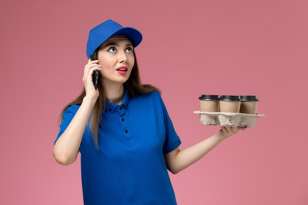 Widok z przodu kurierka w niebieskim mundurze i pelerynie trzymającej filiżanki do kawy i smartfona na różowej ścianie