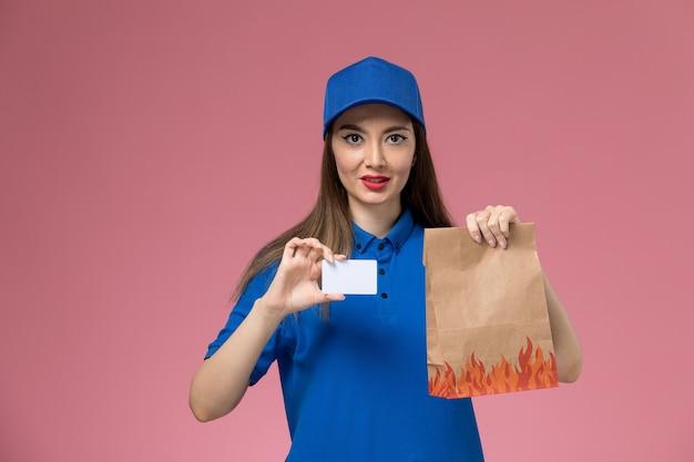 Widok z przodu kurierka w niebieskim mundurze i pelerynie trzymającej kartę i papierowe opakowanie żywności na różowym biurku