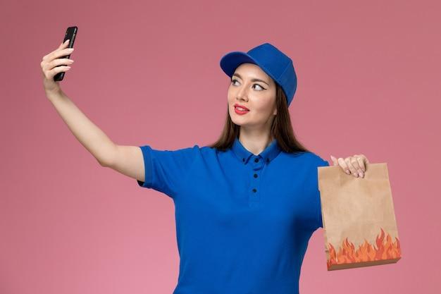 Widok z przodu kurierka w niebieskim mundurze i pelerynie trzymającej telefon i pakiet żywności, robiąc zdjęcie na różowej ścianie