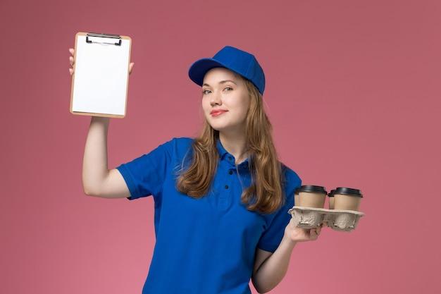Widok z przodu kurierka w niebieskim mundurze trzyma notatnik i filiżanki kawy z uśmiechem na jasnoróżowym biurku