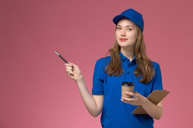 Widok z przodu kurierka w niebieskim mundurze trzymająca brązowy kubek kawy z notatnikiem i długopisem na jasnoróżowym tle mundur służbowy firma dostarczająca