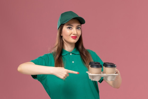 Widok z przodu kurierka w zielonym mundurze i pelerynie trzyma filiżanki kawy dostawy na różowej ścianie usługi mundurowej pani pracy dostawy