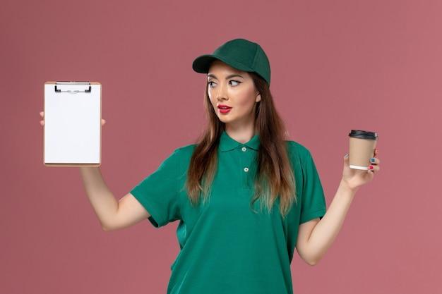 Widok z przodu kurierka w zielonym mundurze i pelerynie trzymająca dostawę filiżankę kawy i notatnik na różowym biurku mundur służbowy praca dostawa pracownik kobieca firma