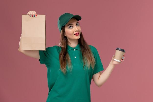 Widok z przodu kurierka w zielonym mundurze i pelerynie trzymająca dostawę filiżankę kawy i pakiet żywności na jasnoróżowym biurku usługa firmy dostawa munduru pracy