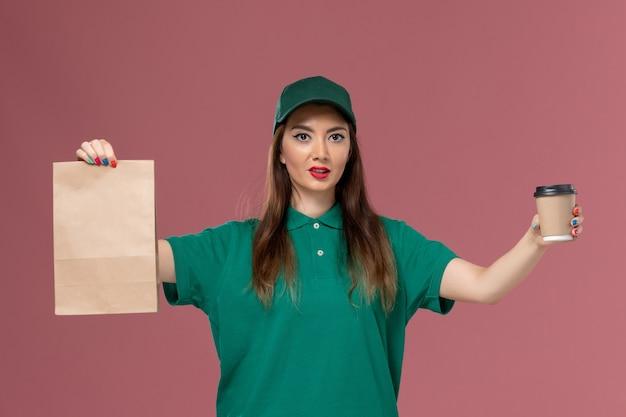 Widok z przodu kurierka w zielonym mundurze i pelerynie trzymająca dostawę filiżankę kawy i pakiet żywności na różowej ścianie dostawa munduru służbowego firmy