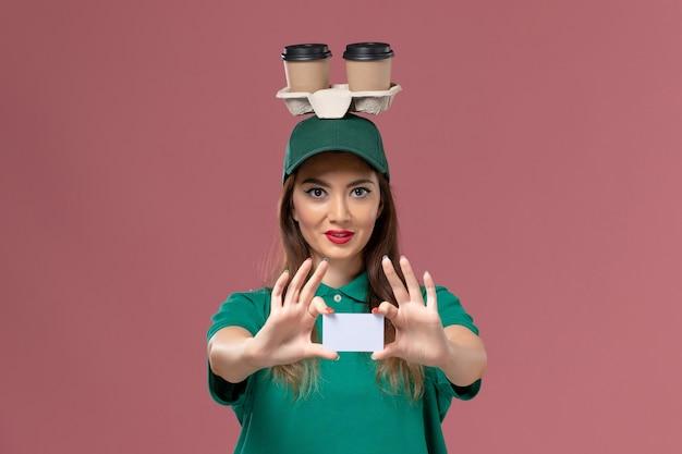 Widok z przodu kurierka w zielonym mundurze i pelerynie trzymająca dostawy filiżanek kawy i karty na różowej ścianie pracownik serwisowy jednolita dostawa
