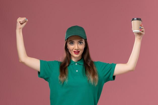 Widok z przodu kurierka w zielonym mundurze i pelerynie trzymająca filiżankę kawy dostawy i wiwatująca na różowej ścianie praca służbowa jednolita dostawa pracy