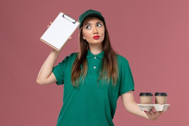 Widok z przodu kurierka w zielonym mundurze i pelerynie trzymająca filiżanki kawy dostawy i notatnik myślący na różowej ścianie usługa jednolita dostawa