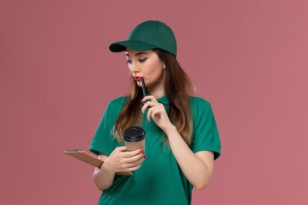 Widok z przodu kurierka w zielonym mundurze i pelerynie trzymającej dostawę filiżankę kawy i notatnik na różowej ścianie praca służbowa usługa jednolita dostawa